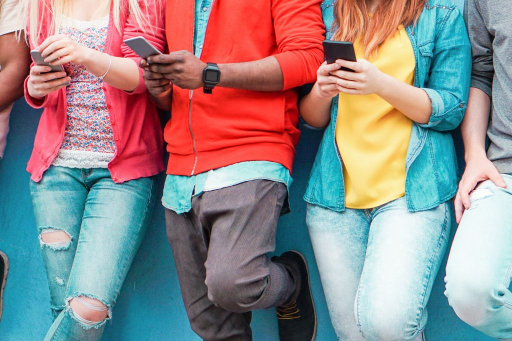 Group of young friends watching smart mobile phones
