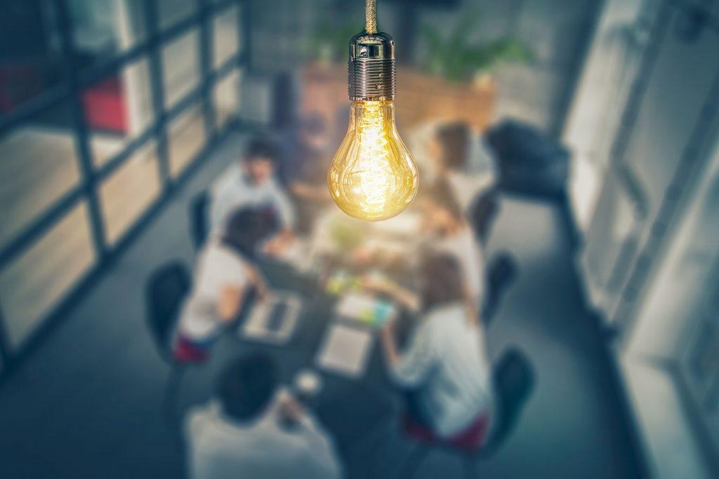 light bulb above creative team brainstorming