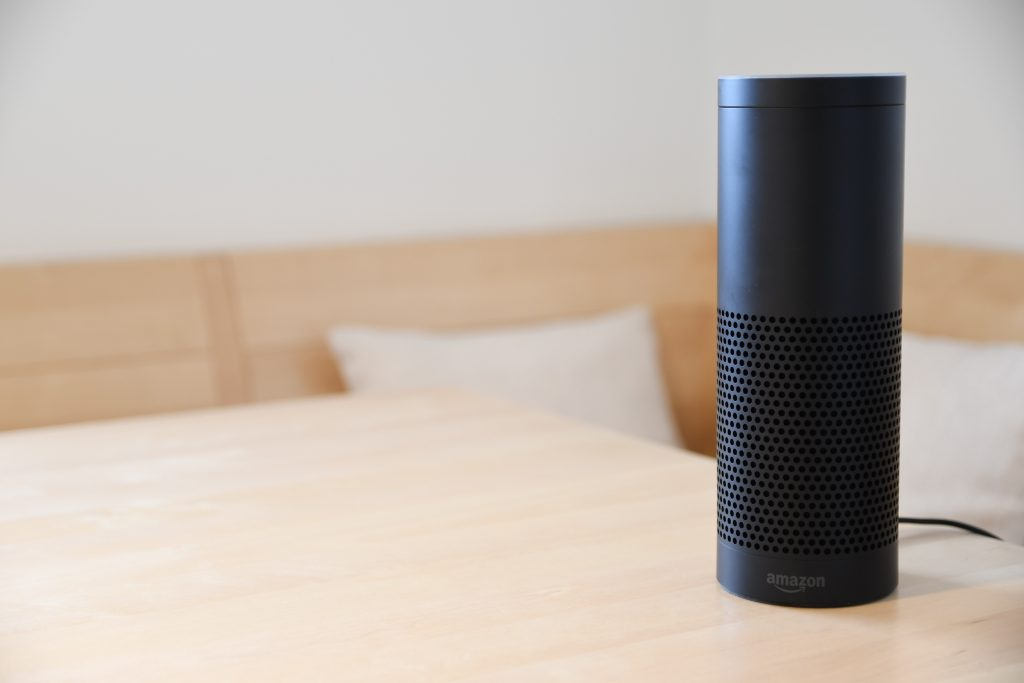a black Amazon Alexa on a wood table